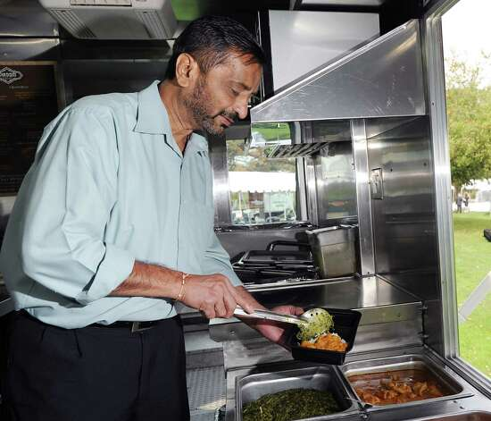Pharat Patel scoops a plate of Indian food in the kitchen of his food truck the Tandoori Express of Greenwich during the second annual Greenwich Food and Wine Festival at Roger Sherman Baldwin Park in Greenwich, Saturday, Oct. 6, 2012. The event benefits the Hole in the Wall Gang Camp, a nonprofit that runs camps for children coping with cancer, sickle cell anemia and other serious illnesses. Photo: Bob Luckey / Greenwich Time