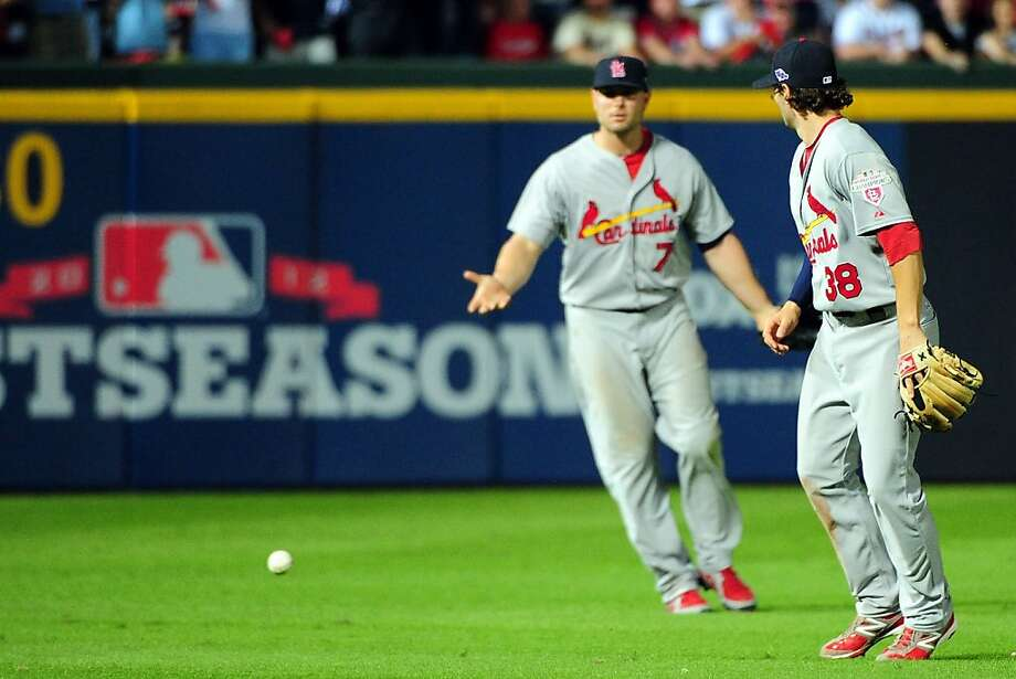 Pete Kozma (right) and Matt Holliday of the Cardinals let Andrelton Simmons' pop fly drop between them. Kozma, the infielder, appeared to have gotten into position to make the catch but pulled away just as the infield fly rule was being called. Photo: Scott Cunningham, Getty Images