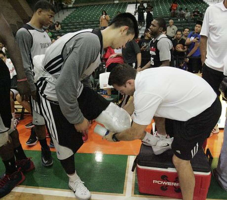Rockets Jeremy Lin get his knee iced by a trainer after the teams intrasquad scrimmage. (Delcia Lopez / Associated Press/The Monitor)