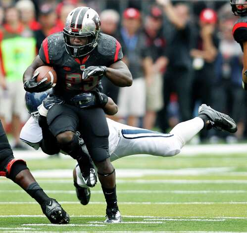 Rutgers running back Jawan Jamison drags a Connecticut defender along as he gains yardage during the second half of an NCAA college football game in Piscataway, N.J., Saturday, Oct. 6, 2012. Rutgers won 19-3. (AP Photo/Mel Evans) Photo: Mel Evans, Associated Press / AP