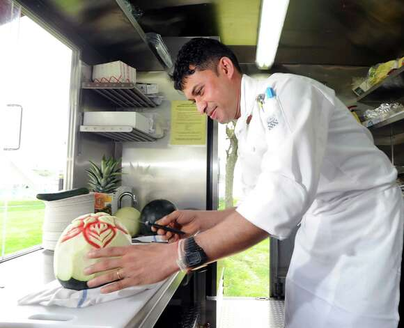 Chef Swarup Hira of the Tandoori Express of Greenwich, a food truck serving Indian food, makes an ornamental carving in a watermelon during the second annual Greenwich Food and Wine Festival at Roger Sherman Baldwin Park in Greenwich, Saturday, Oct. 6, 2012. The event benefits the Hole in the Wall Gang Camp, a nonprofit that runs camps for children coping with cancer, sickle cell anemia and other serious illnesses. Photo: Bob Luckey / Greenwich Time