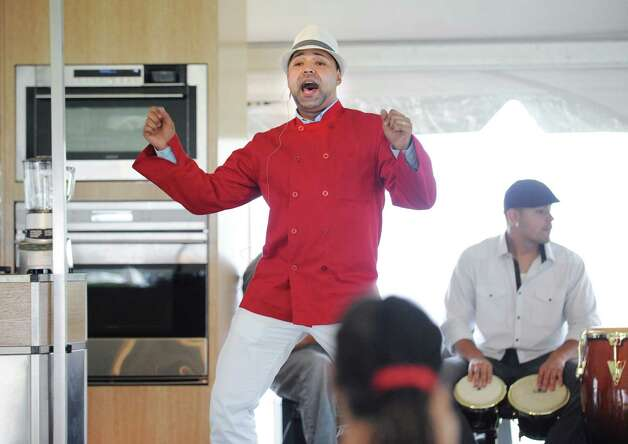 The Sensational Singing Chef Neil Fuentes of New Haven during the second annual Greenwich Food and Wine Festival at Roger Sherman Baldwin Park in Greenwich, Saturday, Oct. 6, 2012. Playing the bongos is Adrian Miranda of the chef's band, Sonido Libre. The event benefits the Hole in the Wall Gang Camp, a nonprofit that runs camps for children coping with cancer, sickle cell anemia and other serious illnesses. Photo: Bob Luckey / Greenwich Time