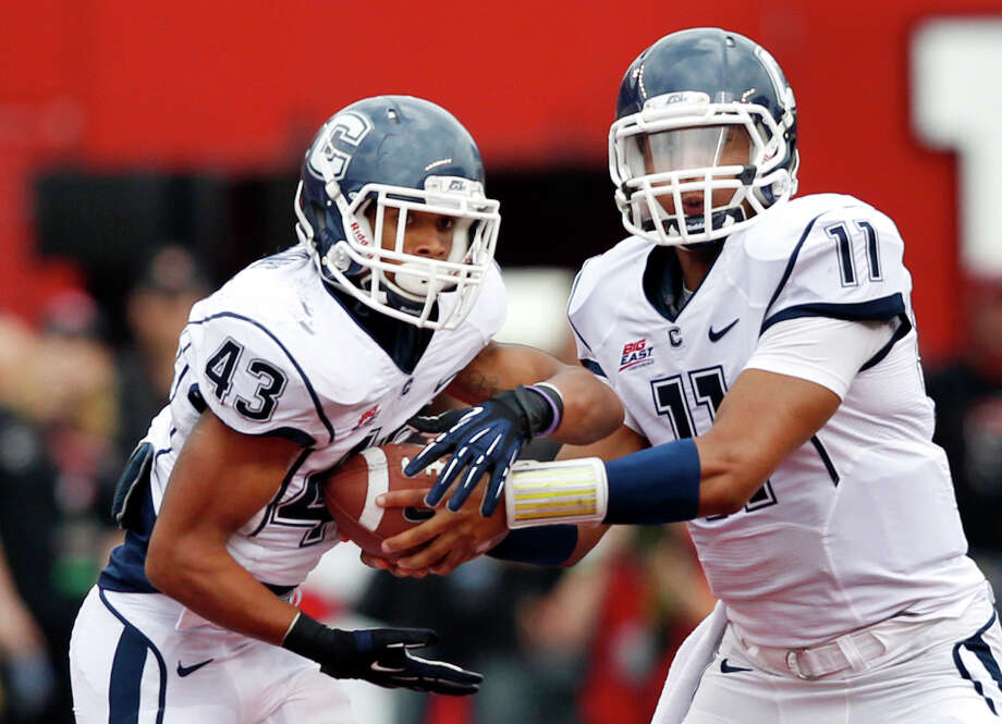 Connecticut quarterback Scott McCummings (11) hands the ball to running back Lyle McCombs (43) during the second half of an NCAA college football game against Rutgers in Piscataway, N.J., Saturday, Oct. 6, 2012.  Rutgers won 19-3. (AP Photo/Mel Evans) Photo: Mel Evans, Associated Press / AP