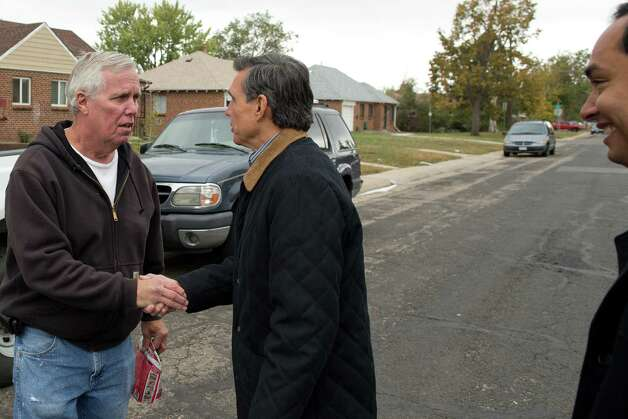 Federico Peña, former Secretary of Transportation and former mayor of Denver, shakes hands with Marvin Crumbliss as he canvases the Athmar Park neighborhood with Texas state Rep. Joaquín Castro (right). The pair were out looking to register people to vote in the Nov. 6 general election in Denver, Saturday, Oct. 6, 2012. Crumbliss, a Denver resident, was already registered to vote. Photo: Justin Edmonds, For The Express-News / © 2012 Justin Edmonds