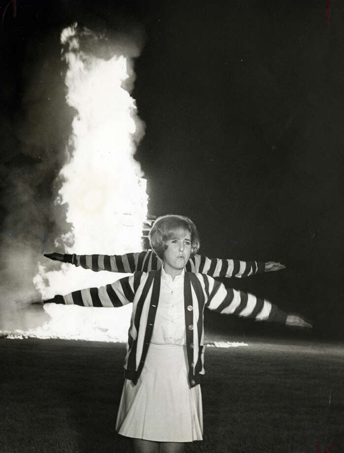 Rice University Cheerleaders Kathy Childers and Billl Leeman (behind) whip up student spirit for the Rice Owls' homecoming football game with Texas A&M at Rice Stadium. Students whooped and cheered before a bonfire fed by scrap lumber in November of 1966. Photo: Houston Chronicle File Photo