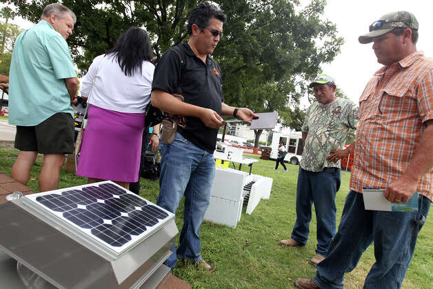 Raciel Juarez, CEO of Texas Green Solar & Wind Solutions, explains solar technology to Oscar Moreno and Ernie Ayala. Photo: Jennifer Whitney, For The Express-News / © Jennifer Whitney