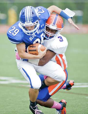 Darien High School tailback Myles Ridder is taken down by Danbury High School's Corey Acosta during a football game at Darien. Saturday, Oct. 6, 2012 Photo: Scott Mullin / The News-Times Freelance