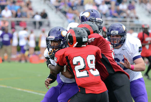 Westhill's Davell Cotterell (7) carries the ball as Central's Richard Hutchinson (29) defends during the football game at Westhill High School on Saturday, Oct. 6, 2012. Photo: Amy Mortensen / Connecticut Post Freelance