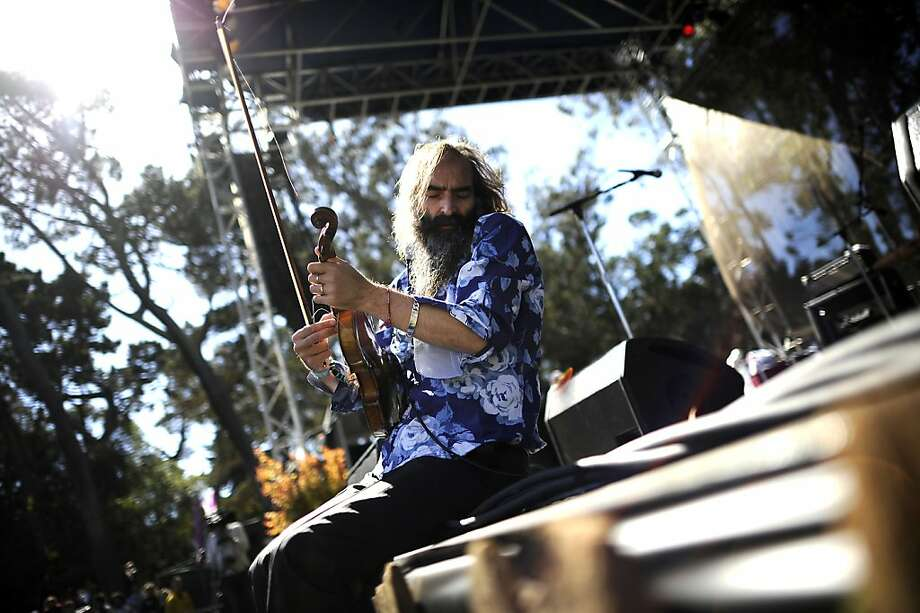 Warren Ellis sits on the edge of the stage as his band Dirty Three plays.  Hardly Strictly Bluegrass festival in Golden Gate Park in San Francisco, CA Friday October 6th, 2012. Photo: Michael Short, Special To The Chronicle