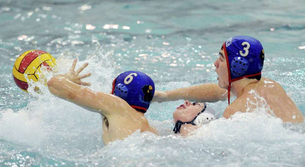 Greenwich defenders Julian Fraser, left, # 6 and Jack Robinson, right, # 3, steamroll a Deerfield player while going for the ball during high school water polo match between Greenwich High School and Deerfield Academy at Greenwich, Saturday afternoon, Oct. 6, 2012.