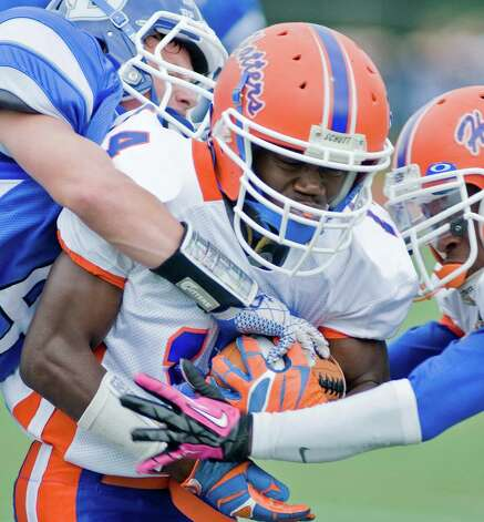 Danbury High School's wide receiver Elijah Amoah protects the ball against Darien High School in a football game at Darien. Saturday, Oct. 6, 2012 Photo: Scott Mullin / The News-Times Freelance