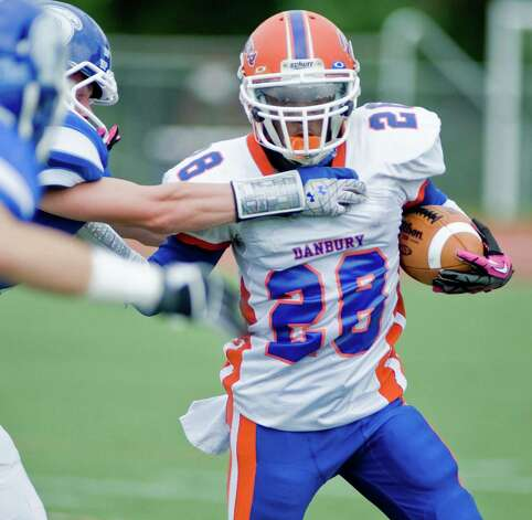 Danbury High School running back Chris Latham tries to cut around Darien High School defenders in a football game at Darien. Saturday, Oct. 6, 2012 Photo: Scott Mullin / The News-Times Freelance