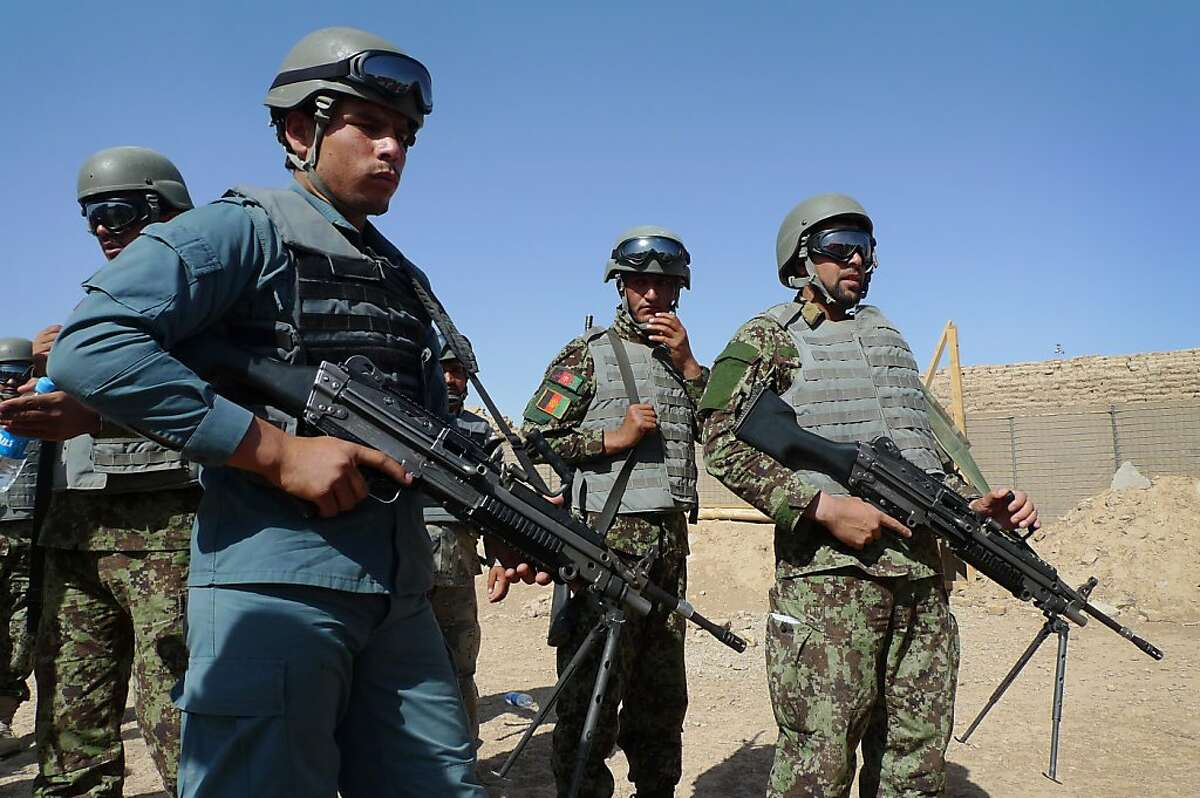 In this June 19, 2012 file photo, Afghan soldiers and a policeman prepare for a mock ambush as part of a training exercise at the U.S. Marine-run Joint Sustainment Academy, Camp Leatherneck in Helmand, south of Kabul. The U.S. suspects the Haqqani insurgent network, which has ties to al-Qaida and is based in Pakistan, is a driving force behind many of the
