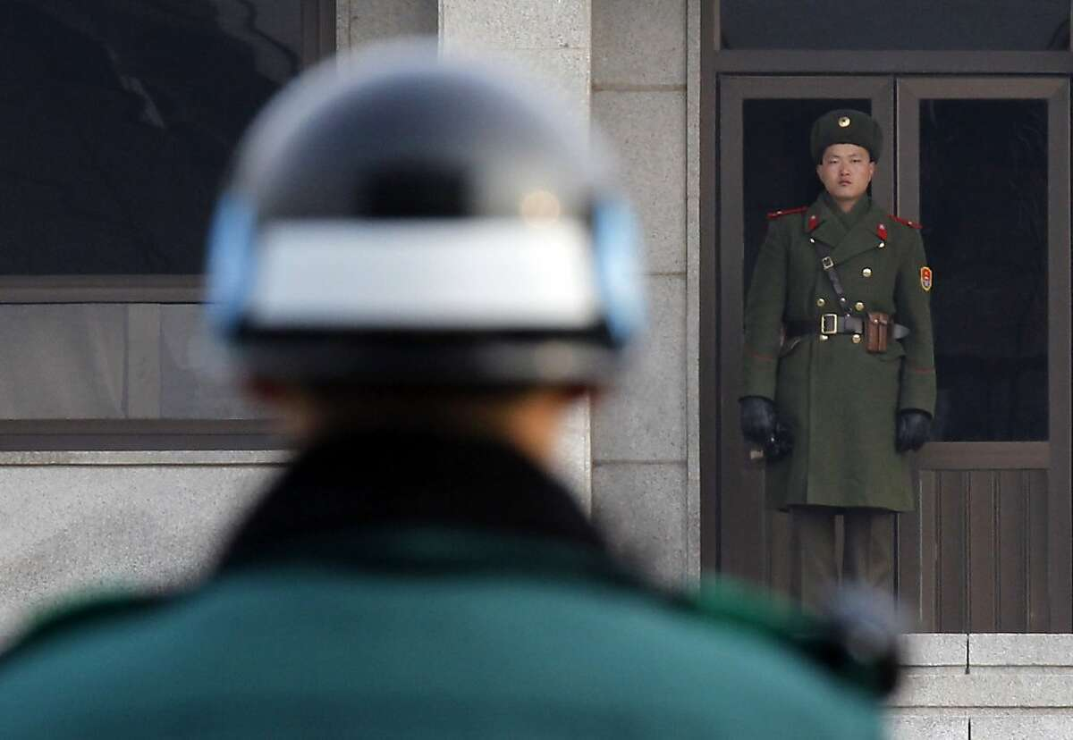 In this Dec. 28, 2011 file photo, a North, right, and a South Korean soldier look at each other's sides at the Panmunjom (DMZ) that separates the two Koreas since the Korean War, in Paju, South Korea. A North Korean soldier killed two of his superiors Saturday, Oct. 6, 2012, and defected to South Korea across the countries' heavily armed border in a rare crossing that prompted South Korean troops to immediately beef up their border patrol, officials said. The soldier shot his platoon and squad leaders before crossing the western side of the Demilitarized Zone at around noon, a Defense Ministry official said, citing the soldier's statement after he was taken into custody by South Korean border guards. (AP Photo/Kim Kyung-hoon, Pool)