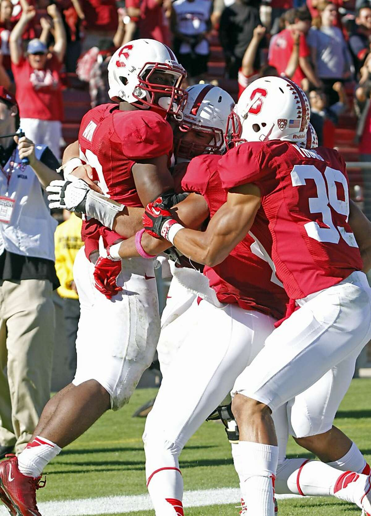 Stanford's Stepfan Taylor, left, celebrates with teammates after scoring the game-winning touchdown in overtime against Arizona during an NCAA college football game in Stanford, Calif., Saturday, Oct. 6, 2012. Stanford beat Arizona 54-48. (AP Photo/George Nikitin)