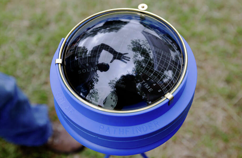 ONTility solar trainer and consultant Eddie Haynes (left) of Houston is reflected while discussing the use of a device called a Solar Pathfinder at Solar Fest at Maverick Park on May 1, 2010. Haynes said the device helps people find the optimal position for their solar panels to get the most efficiency. ONTility was one of many vendors on hand to showcase the latest in solar energy technology. Photo: Kin Man Hui, San Antonio Express-News / kmhui@express-news.net
