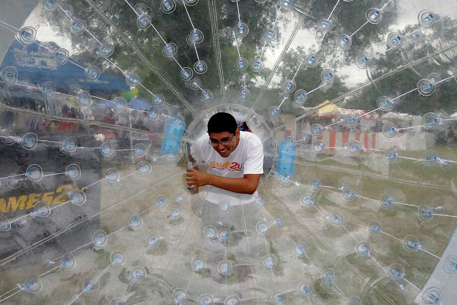 "Adam Apolinar looks over the interior of the ""Hamster Ball"" at Solar Fest at Maverick Park on May 1, 2010. The ball is inflated with air and people can jump inside and propel themselves. Photo: Kin Man Hui, San Antonio Express-News / kmhui@express-news.net"