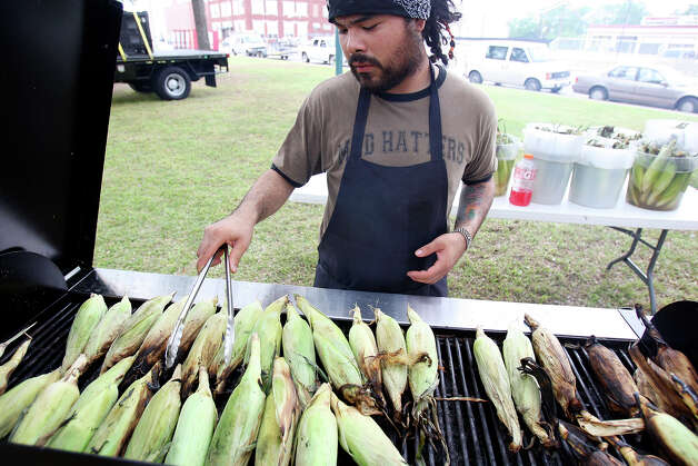 Justin Siller roasts corn for the Mad Hatters booth during Solar Fest on May 2, 2009, at Maverick Park. Photo: Edward A. Ornelas, San Antonio Express-News / eaornelas@express-news.net