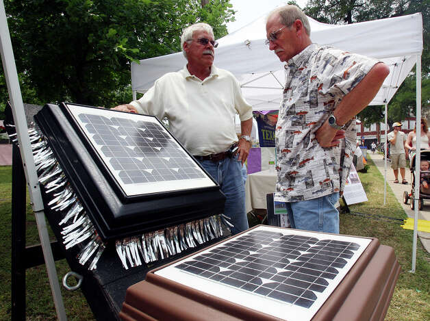 Gary Trainer (left) shows George Moravits a solar attic fan at the Solar Texas booth during Solar Fest on May 2, 2009, at Maverick Park. Photo: Edward A. Ornelas, San Antonio Express-News / eaornelas@express-news.net