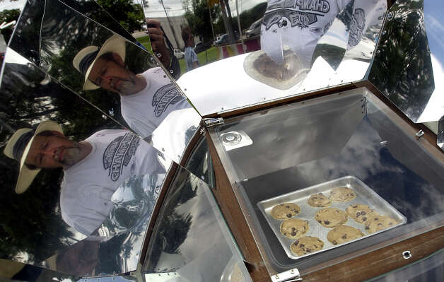 Pete Stai, seen in the reflection, checks out a solar oven as it bakes chocolate chip cookies at the Texas Solar Energy Society's display at Solar Fest on June 6, 2004, at Maverick Park. Photo: San Antonio Express-News File Photo / SAN ANTONIO EXPRESS-NEWS