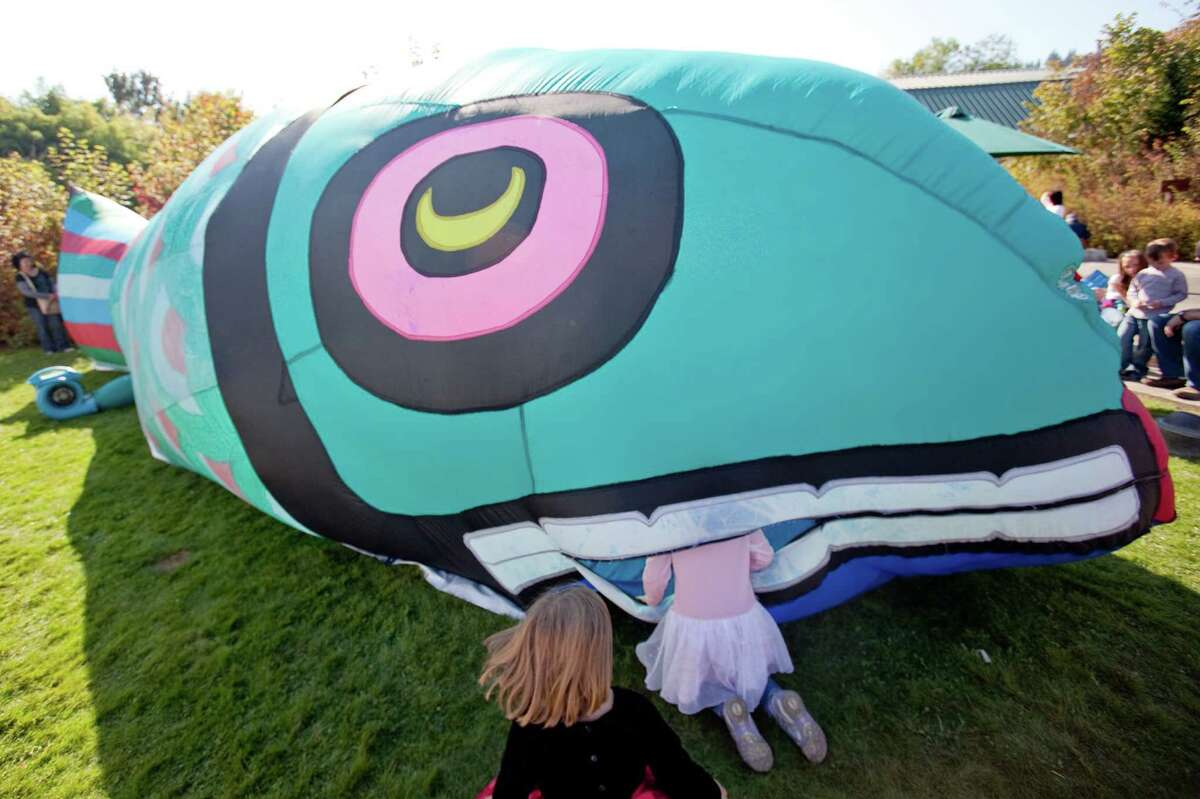 Youngsters peek into an inflatable salmon hosting story time during Issaquah Salmon Days on Saturday, October 6, 2012. The annual festival kicks off with a parade and celebrates the return of the salmon to Issaquah Creek.