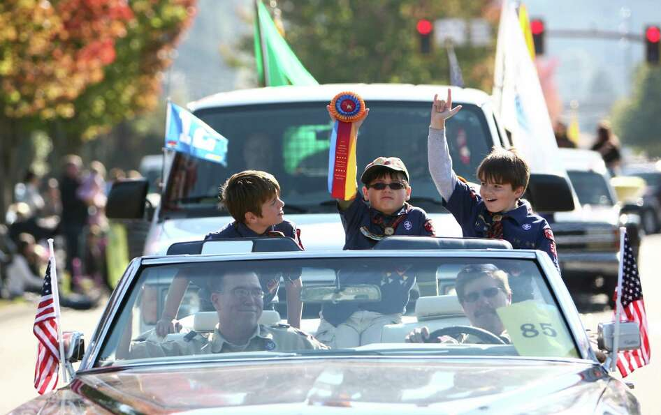 Cub Scouts ride in a car during the Issaquah Salmon Days Parade on Saturday, October 6, 2012. The an