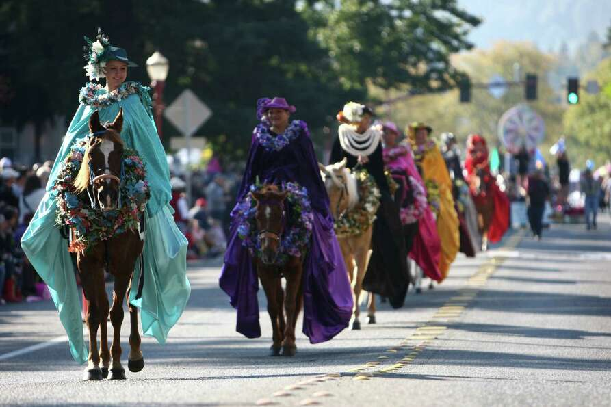 The Kau' Lio Pa'u Riders make their way along Front Street during Issaquah Salmon Days on Saturday,