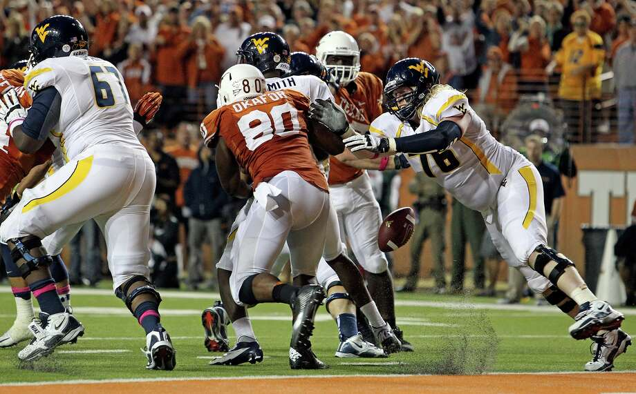 Longhorn defender Alex Okafor pressures Geno Smith and knocks the ball loose to be recovered by teammates for a touchdown as Texas hosts West Virginia at Darrel K. Royal Texas Memorial Stadium in Austin on October 6, 2012. Photo: Tom Reel, San Antonio Express-News / ©2012 San Antono Express-News