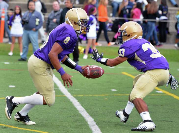 Amsterdam's #8 Geovanni Rodriguez hands off to #33 Hector Diaz during Saturday's game against Burnt