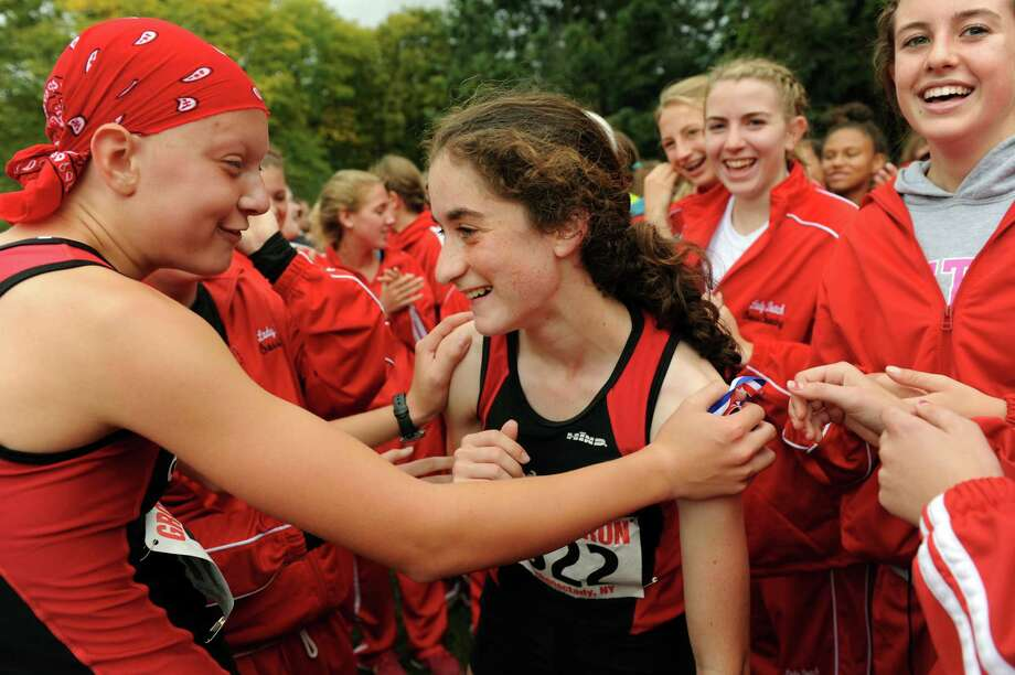 Guilderland's Emily Burns, center, celebrates placing first in the Division I Girls Grout Run with her teammates on Saturday, Oct. 6, 2012, at Central Park in Schenectady, N.Y. (Cindy Schultz / Times Union) Photo: Cindy Schultz / 00019470A