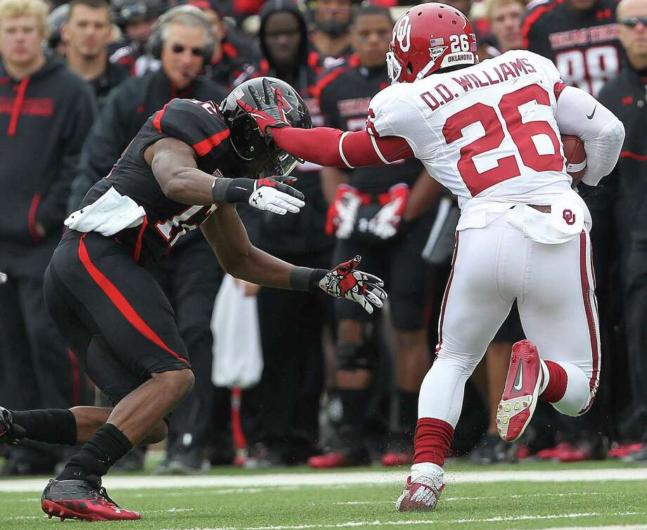 Oklahoma's Damien Williams gets pushy with Texas Tech's D.J. Johnson. Photo: Stephen Spillman / Lubbock Avalanche-Journal