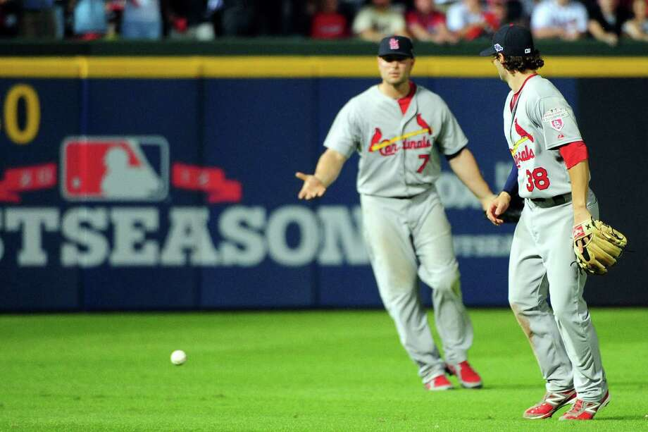 The Cardinals' Matt Holliday (7) and Pete Kozma (38) appear confused as Andrelton Simmons' pop fly falls between them in the outfield in the eighth inning Friday. Umpire Sam Holbrook ruled Simmons out under the infield fly rule. Photo: Scott Cunningham / 2012 Getty Images