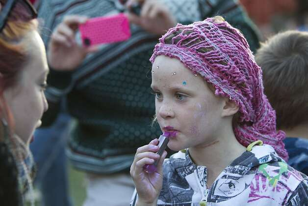 Kelli Bratvold (left) helps 5-year-old Mya Dunne put on lipstick while relaxing by the Arrow Stage at Hardly Strictly Bluegrass at Golden Gate Park in San Francisco, Calf., on Saturday, October 6, 2012. Photo: Laura Morton, Special To The Chronicle