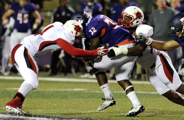 Cardinals take down Northwestern State running back Robert Walker, 32, during Northwestern State football game against Lamar University at Northwestern State University on Saturday, October 6, 2012. Photo taken: Randy Edwards/The Enterprise