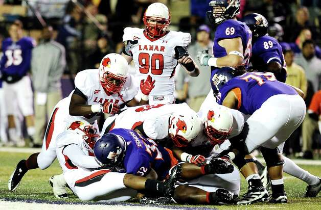 Cardinals pile up on Northwestern State running back Robert Walker, 32, during Northwestern State football game against Lamar University at Northwestern State University on Saturday, October 6, 2012. Photo taken: Randy Edwards/The Enterprise