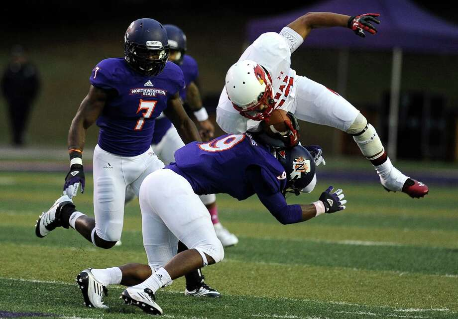 Lamar  wide receiver Reggie Begelton is knocked off his feet on an attempt for first down during Northwestern State football game against Lamar University at Northwestern State University on Saturday, October 6, 2012. Photo taken: Randy Edwards/The Enterprise