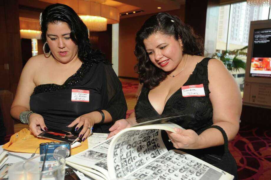 Carmen Perez (left) and Sandra Diaz look over a yearbook during the Thomas Jefferson High School Class of 1992 Reunion at the Grand Hyatt on Saturday, Oct. 6, 2012. San Antonio Mayor Julián Castro and his brother, Joaquín, were members of the class. Photo: Billy Calzada, San Antonio Express-News / © San Antonio Express-News