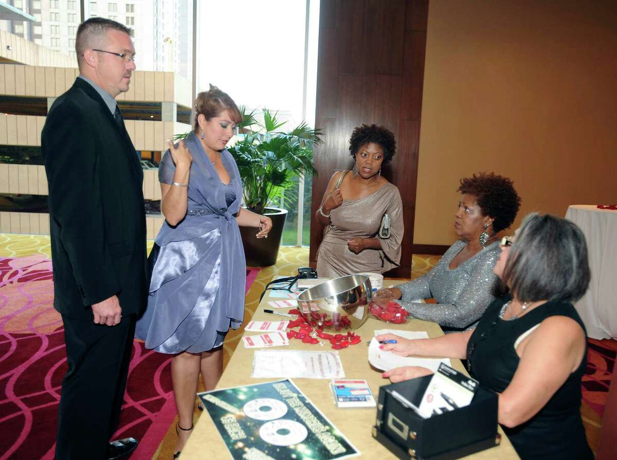 Eddie Michalik (left) and his wife, Jessica, who was the mascot at Thomas Jefferson High School, are greeted by Monique Broadnax (center) and her mother, Hortense, and Gloria Valenzuela (right) during the Thomas Jefferson High School Class of 1992 Reunion at the Grand Hyatt on Saturday, Oct. 6, 2012. San Antonio Mayor Julián Castro and his brother, Joaquín, were members of the class.
