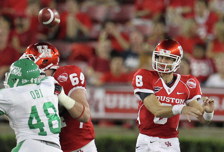 Houston's David Piland, right, looks to complete a pass as his offensive lineman Ty Cloud, center, protects him from North Texas defensive end K.C. Obi during the second quarter of an NCAA college football game against North Texas, Saturday, Oct. 6, 2012, in Houston. (AP Photo/Houston Chronicle, Nick de la Torre) Photo: Nick De La Torre, Associated Press / Houston Chronicle