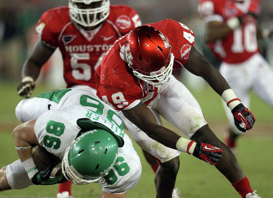 North Texas tight end Drew Miller, left, is hit hard by University of Houston linebacker Derrick Matthews during the third quarter of a NCAA football game Saturday, Oct. 6, 2012, in Houston. Photo: Nick De La Torre, Houston Chronicle / © 2012  Houston Chronicle