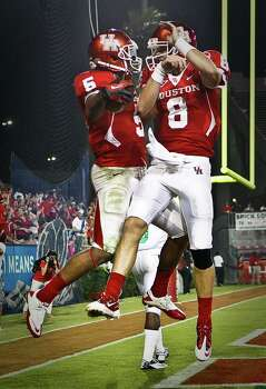 Houston running back Charles Sims, left, celebrates his touchdown run with quarterback David Piland during the second quarter of an NCAA college football game against North Texas, Saturday, Oct. 6, 2012, in Houston. (AP Photo/Houston Chronicle, Nick de la Torre) Photo: Nick De La Torre, Associated Press / Houston Chronicle