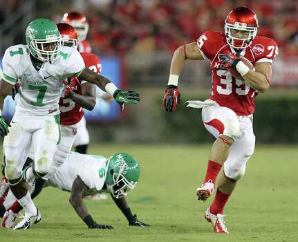 University of Houston running back Kenneth Farlow, right, gets past University of North Texas safety Devante Davisfor a touchdown run during the second quarter of a NCAA football game Saturday, Oct. 6, 2012, in Houston. Photo: Nick De La Torre, Houston Chronicle / © 2012  Houston Chronicle