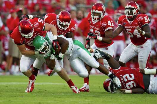 University of Houston defensive lineman Zeke Riser, left, and the rest of the Cougar defense keeps University of North Texas running back Brandin Byrd in check on a running play during the second quarter of a NCAA football game Saturday, Oct. 6, 2012, in Houston. Photo: Nick De La Torre, Houston Chronicle / © 2012  Houston Chronicle