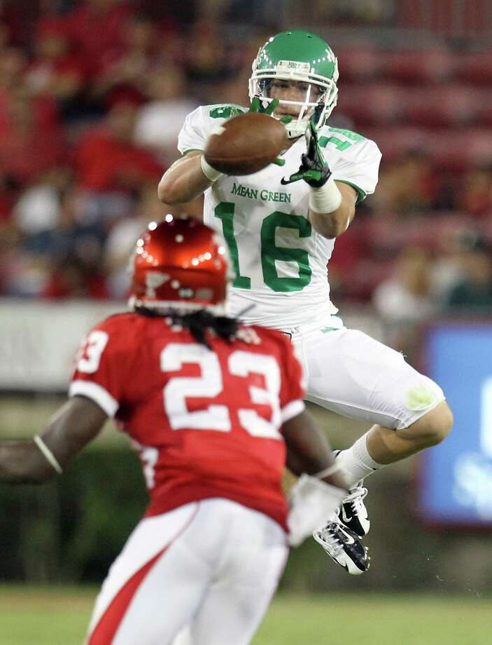 Derrick Thompson of the University of North Texas keeps his eyes on a pass as Trevon Stewart closes in during the second quarter of a NCAA football game Saturday, Oct. 6, 2012, in Houston. Photo: Nick De La Torre, Houston Chronicle / © 2012  Houston Chronicle