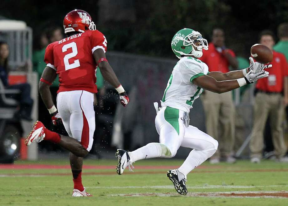 North Texas receiver Ivan Delgado, right, makes a midfield catch as he gets behind Houston's D.J. Hayden during the second quarter of an NCAA college football game against North Texas, Saturday, Oct. 6, 2012, in Houston. (AP Photo/Houston Chronicle, Nick de la Torre) Photo: Nick De La Torre, Associated Press / Houston Chronicle