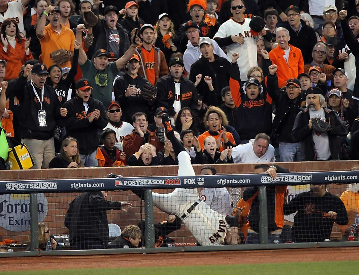 Giants first baseman Brandon Belt goes over the railing to catch a foul ball in the first inning. Belt caught the ball and was not injured on the play. The San Francisco Giants played the Cincinnati Reds at AT&T Park in San Francisco, Calif., in Game 1 of the National League Division Series.