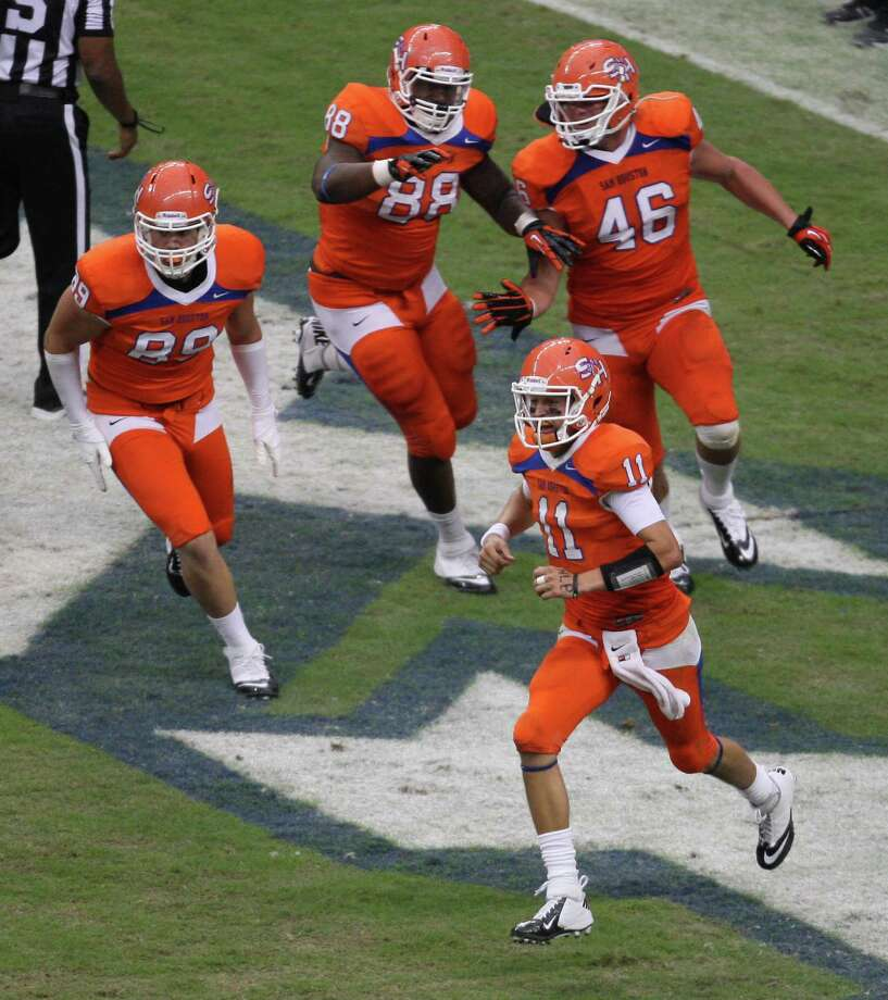 Sam Houston State's Brian Bell (11) runs off the field with teammates Shane Young (89), K.J. Williams (88) and J.D. Stanley after scoring a touchdown on a fake field goal during the second half of the Battle of the Piney Woods college football game against SFA, Saturday, October 6, 2012 at Reliant Stadium in Houston, TX. Photo: Eric Christian Smith, For The Chronicle