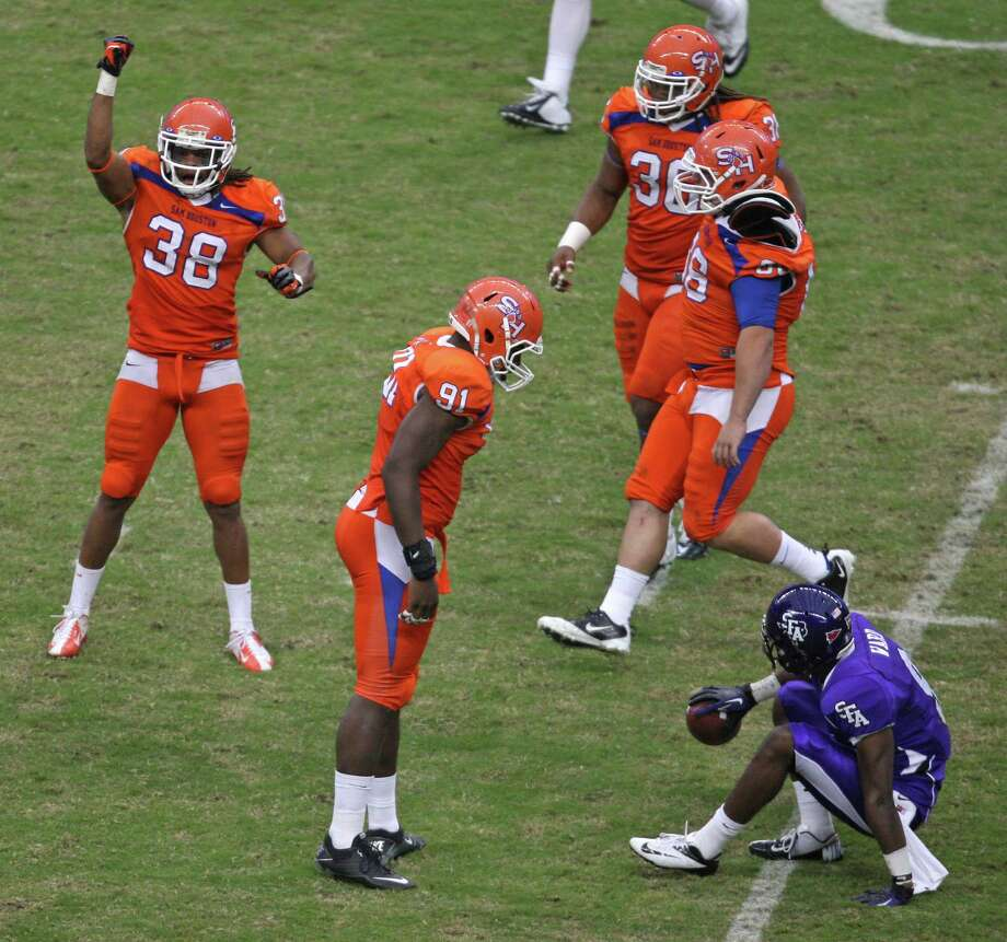 Sam Houston State's Darnell Taylor (38) celebrates his tackle of SFA's DJ Ward (9) as teammate Preston Sanders (91) stares Ward down. Photo: Eric Christian Smith, For The Chronicle