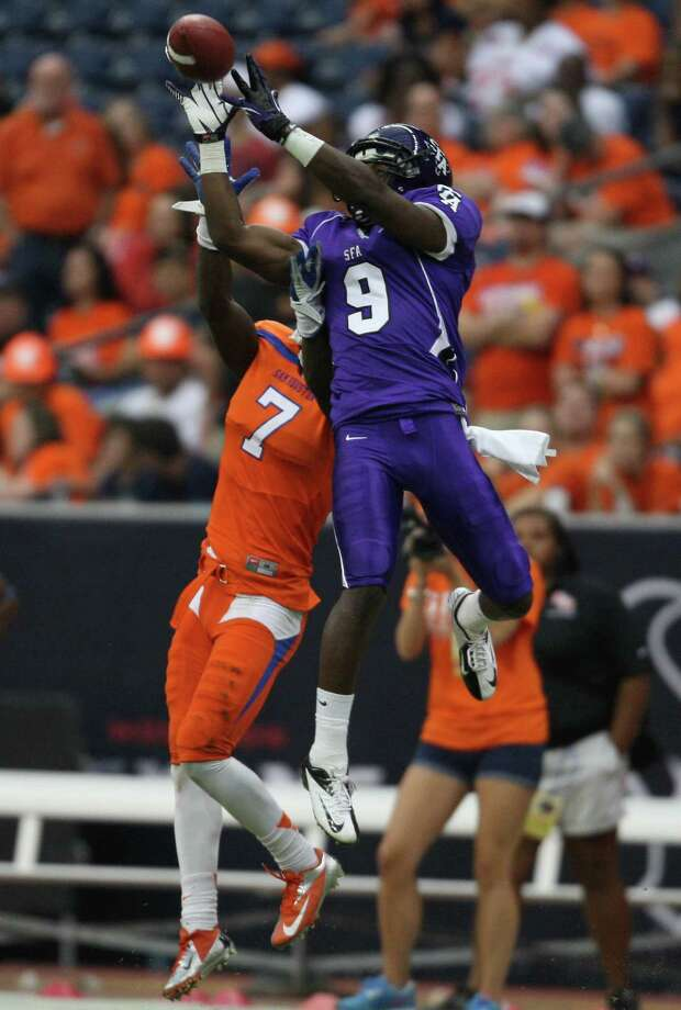 SFA's DJ Wrad (9) makes a reception over Sam Houston State's Dax Swanson during the second half of the Battle of the Piney Woods college football game, Saturday, October 6, 2012 at Reliant Stadium in Houston, TX. Photo: Eric Christian Smith, For The Chronicle