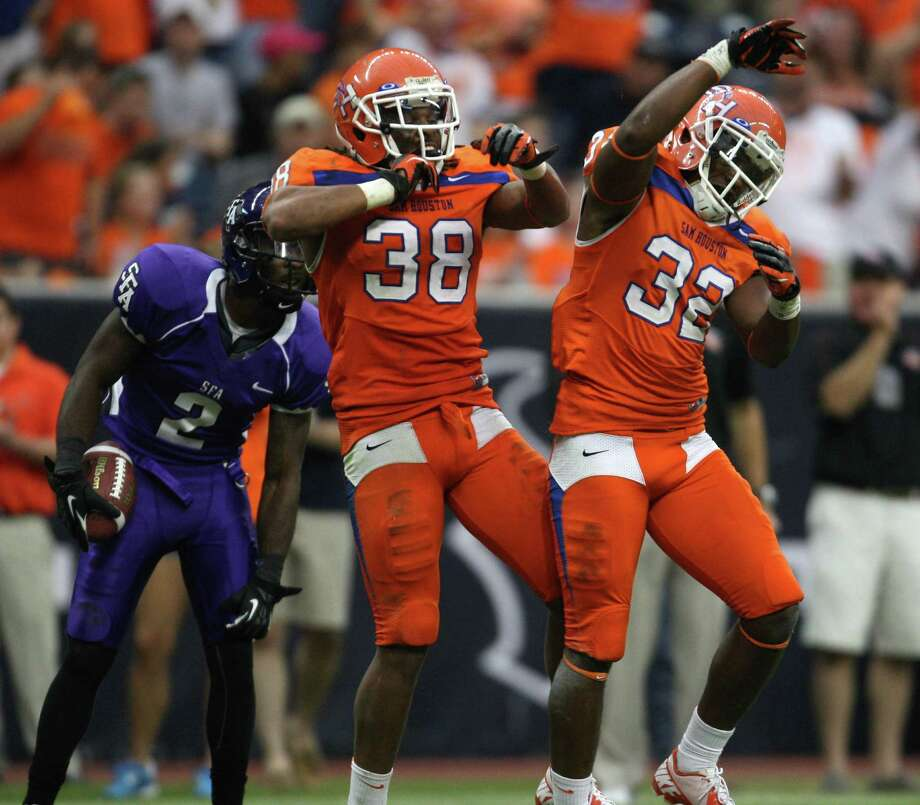 Sam Houston State's Darnell Taylor and Kenneth Jenkins celebrate Jenkins' tackle of SFA's Mike Brooks during the second half. Photo: Eric Christian Smith, For The Chronicle